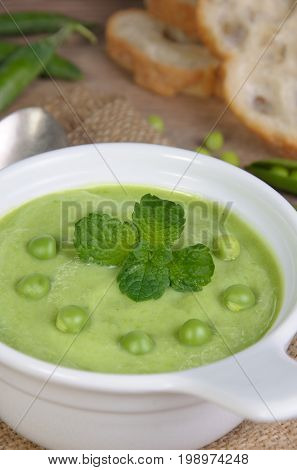 A plate of soup puree of green peas with mint on a table