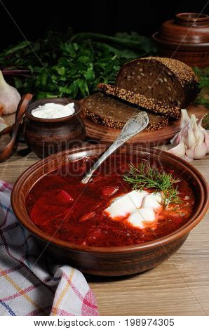 Borscht-vegetable beetroot soup on the table with slices of rye cereal bread and gluten of sour cream garlic and herbs. Rustic style.