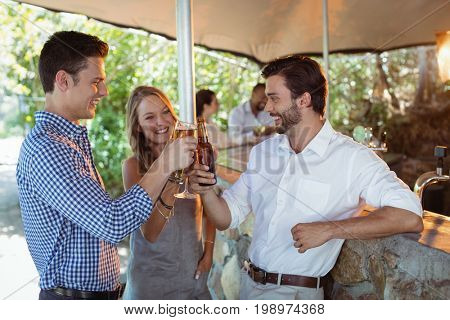 Smiling friends toasting glass and bottle of alcohol at counter in restaurant
