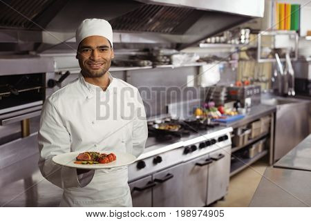 Portrait of smiling chef holding delicious dish in kitchen