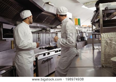 Chefs interacting with each other in kitchen at restaurant