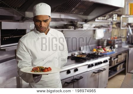 Chef holding delicious dish in kitchen at restaurant
