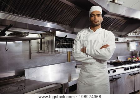 Portrait of confident chef standing with arms crossed in commercial kitchen at restaurant