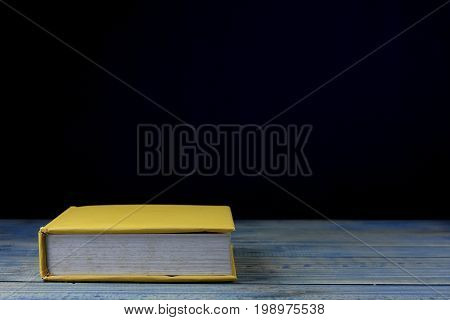 book on wood table and black background concept as opening paper will see knowledge of the world learning by yourself and improve your life