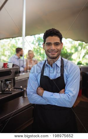 Portrait of smiling male waiter standing with arms crossed in the restaurant