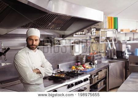 Thoughtful chef standing in commercial kitchen at restaurant