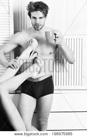 Bearded man short beard. Caucasian sexy macho man with moustache holding coffee cup with female legs on strong muscular torso on athletic body in boxer brief on white wooden studio background