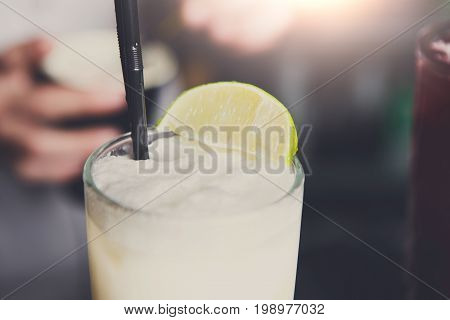 Closeup of frothy coconut pina colada cocktail with lime slice, blurred bar background.