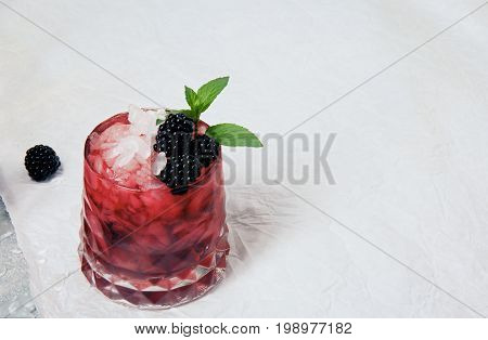 Summer coctail with ice cubes, fresh green mint and sappy blackberries in a pink glass on a white background, copy space, blackberry on a white table-cloth.