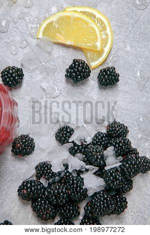Closeup of fresh blackberries mixed with pieces of ice and slices of sappy lemon on a grey moist table with drops of water on a grey background.