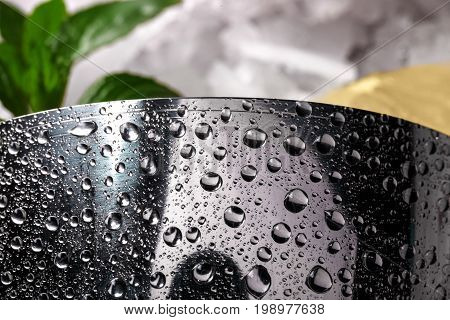 Closeup of a silver shiny metallic shaker with drops of water, green fresh leaves of mint on a light blurred background, beverages for a healthy diet, summer cocktails.