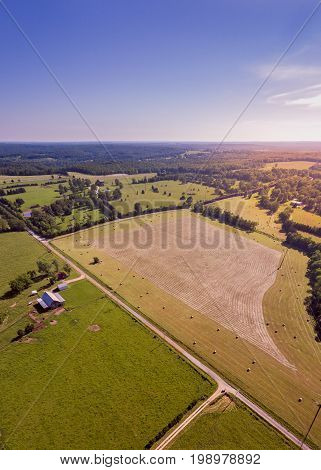 Aerial view of Midwestern farm with cut hay and finished hay bales