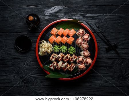 Japanese Cuisine. Sushi Set On A Round Plate Over Dark Wooden Background.