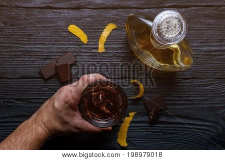 Man's hand holds a glass. A bottle of cognac on a wooden table.