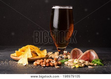 A moist glass of brown ale, with crunchy crisps, sappy tender slices of bacon, handfuls of peanuts, hazelnuts and pistachios on a dark background.