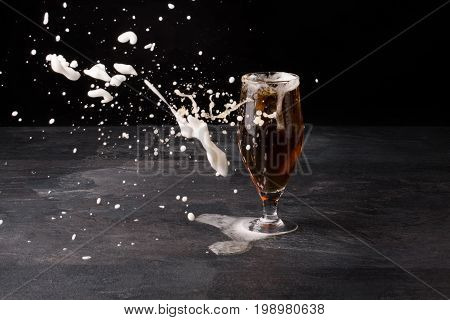 A moist glass of beer filled up with brown ale and white light foam blowed away on a stone table on a dark background, white foam in the air, copy space. Alcohol drink.