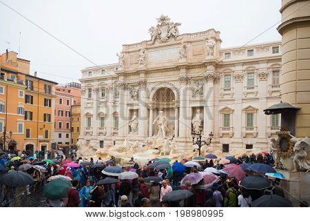 ROME ITALY - OCTOBER 18 2016: Famous Trevi fountain on a rainy day surrounded by lots of tourists with umbrellas