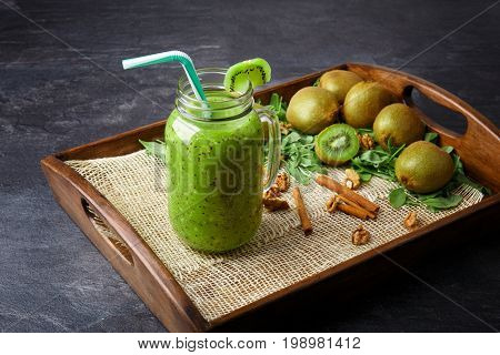 Close-up of a cold kiwi beverage on a dark gray background. A cocktail in a mason jar with a colorful straw. Colorful kiwis, cinnamon sticks and mint leaves next to a cool drink in a wooden tray.