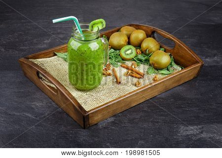 Close-up of a refreshing kiwi drink on a gray stone background. A cocktail in a mason jar with a colorful straw. Colorful kiwis, cinnamon sticks and mint leaves next to a cool drink on a wooden tray.