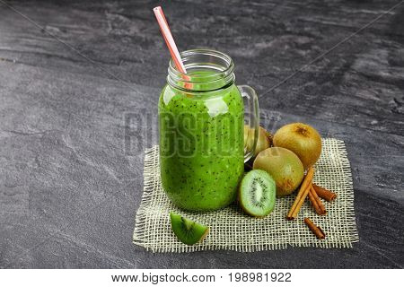 Close-up of a green kiwi beverage on a gray stone background. A cocktail in a mason jar with a colorful straw. Colorful kiwis and cinnamon sticks next to a cool drink. Copy space.