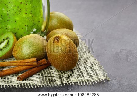 Macro picture of light brown kiwi fruits with aromatic cinnamon on a gray table background. A cold kiwi milkshake in a glass jar next to natural fruits. Vegetarian ingredients. Copy space.