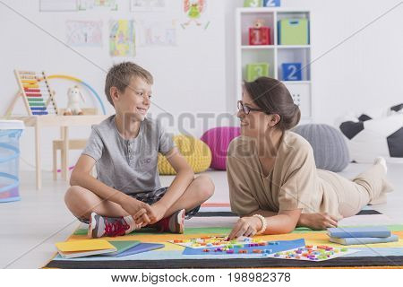 Smiling Boy Sitting On Floor Talking To Therapist
