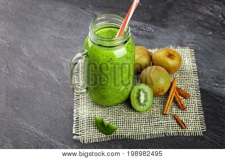 Top view of a green kiwi beverage on a gray stone background. A cocktail in a mason jar with a colorful straw. Colorful kiwis and cinnamon sticks on a cream fabric mesh. Copy space.