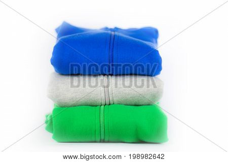 stack of sweater clothes isolated on white background.Pile of clothes on table.