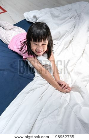 Happy asian kid just woke up on her blue and white bed