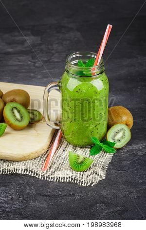A close-up of a transparent mason jar of refreshing kiwi shakes with a straw. Chopped kiwis on a cutting desk and peppermint on a black table background. Green juices full of nutrients.