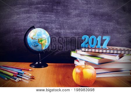 School supplies with numbers 2017 on a stack of books and an apple on blackboard background with copyspace for your text, design. Back to school concept for banner, promotion, web.