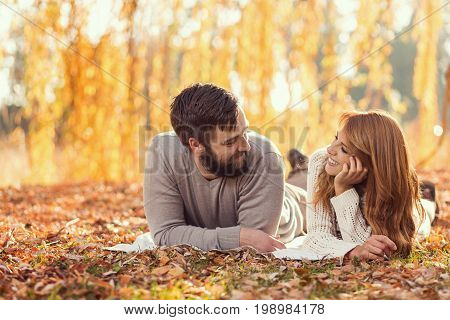 Young couple in love lying on a fallen autumn leaves under a tree in a park and enjoying a wonderful autumn day