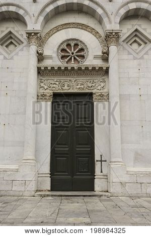 LUCCA, ITALY- AUGUST 15 2015: Architectural close up of the doorway to San Michele church in Lucca Italy