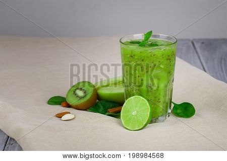 Close-up of a refreshing kiwi beverage on a beige table-cloth and wooden table. A cocktail with fresh fruits on a gray background. Colorful kiwi, nuts, lime and apple half full of vitamins. Copy space.