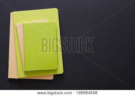 Stylish mockup with set of green notebooks on black background with copy space, flat lay, concept of start-up and stationery supplies