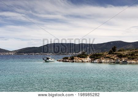 Ship at berth on the background of rocks and the sea on a sunny, summer day