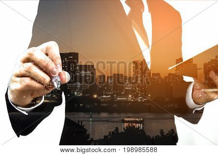 Businessman holding memo and ready to write down with big town or city in the background. Double exposure panoramic view contemporary megalopolis background orange sun light business concept