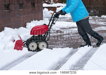 Man cleaning driveway after a snow storm, Snow removal equipment working on the street, Cleaning of streets from snow, It's snowing, Tractor sweeping the street.