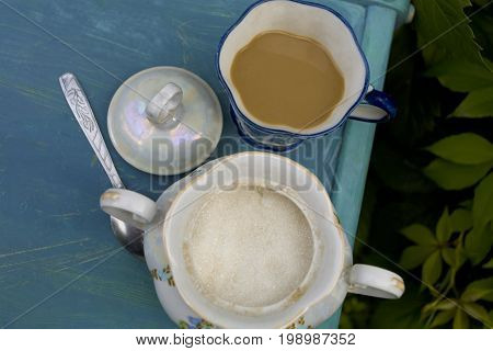 Overhead cropped photo of a sugar bowl with tea or coffee cup on the top of old wooden table. Outdoor shot