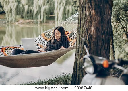 Young Female Freelancer Working On Laptop While Lying On A Hammock Near A Lake, Hipster Woman Restin