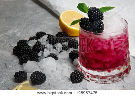 Refreshing cocktail with fresh green mint and sappy blackberries in a pink glass on a grey background, blackberry, slice of lemon and a leaves of mint on a white table-cloth, closeup.