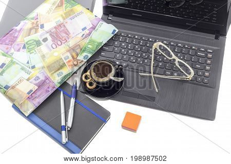 Business still life. Laptop, glasses, pen, notebook and cup of coffee on a table close-up.
