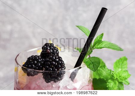 Close-up of a summer cold fruit coctail with ice cubes, blackberries and green fresh leaves of mint, black drinking straw on a light gray background.