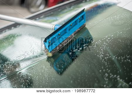 People cleaning car glass using cleaning brush, Cleaning brush on car at carwash, Selective focus