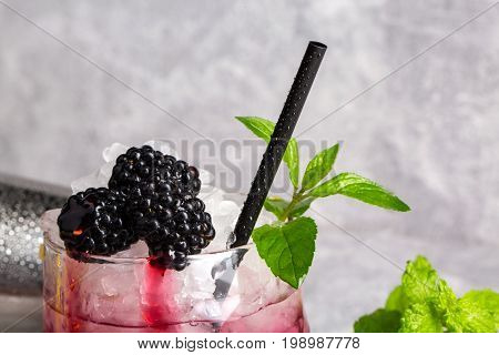 Close-up of summer fresh cocktail with sappy blackberries, ice cubes, green leaves of mint and black moist drinking straw on a grey light background. Summer beverages.