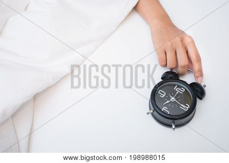 Hand under blanket reaching out for alarm clock, Closeup on woman hand reaching to turn off alarm clock, Selective focus