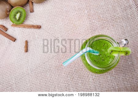 Top view of a mason jar full of kiwi smoothie with striped straw and a slice of green fresh kiwi on a white napkin on a light brown wooden background, cinnamon and kiwis on a wooden table.