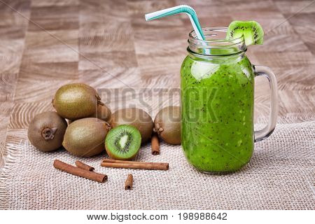 A mason jar full of kiwi smoothie with a striped drinking straw and a slice of green fresh kiwi standing on a white napkin. Cinnamon, and kiwi on a light wooden background. Copy space.