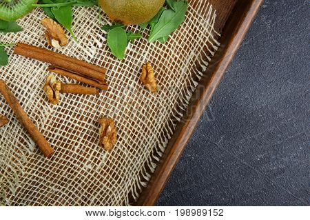 Close-up of sticks of sinnamon and walnuts with green leaves lying on a white napkin on a wooden tray on a dark stone background, top view.