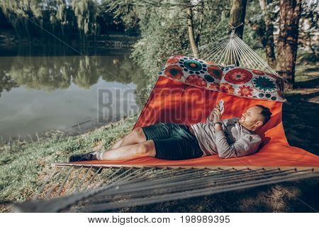 Handsome man relaxing on a hammock on a camping trip stylish hipster man lying on a hammock thinking and looking at phone near a lake relaxation concept
